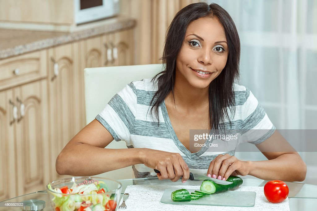 Hermosa mujer Cortando pepino en la cocina moderna para la ensalada : Foto de stock