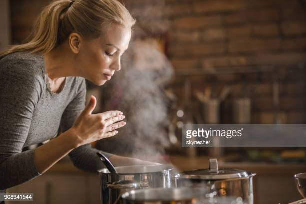 Beautiful woman smelling delicious lunch she is preparing in the kitchen.