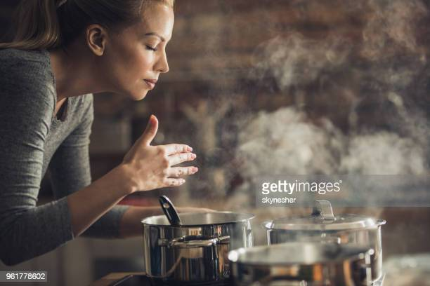 beautiful woman smelling delicious lunch she is preparing in the kitchen. - tasting stock pictures, royalty-free photos & images