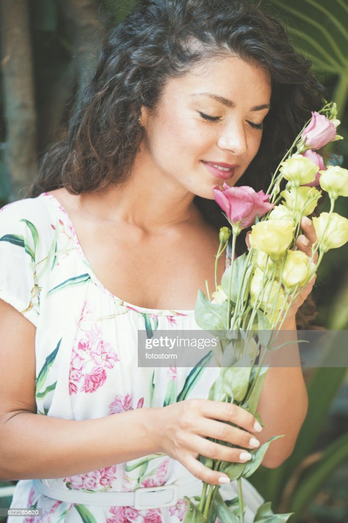 Beautiful woman smelling roses : Stock Photo