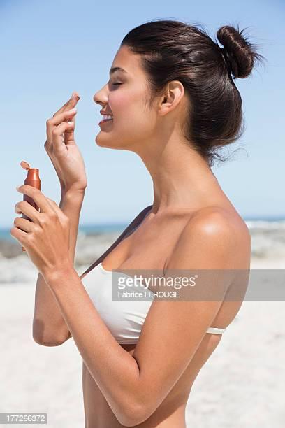 Beautiful woman smelling suntan lotion on the beach