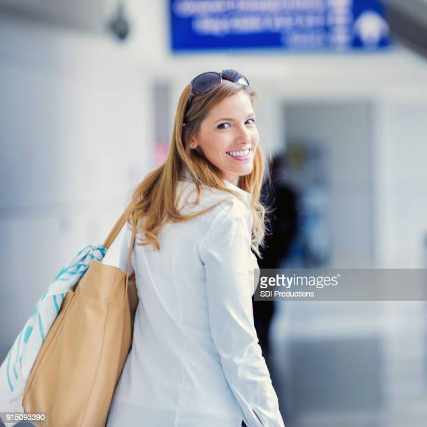 Beautiful woman smiles at camera while leaving on a trip
