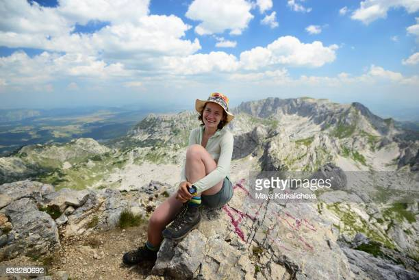 Beautiful woman smiling at the photographer on top of Bobotov Kuk