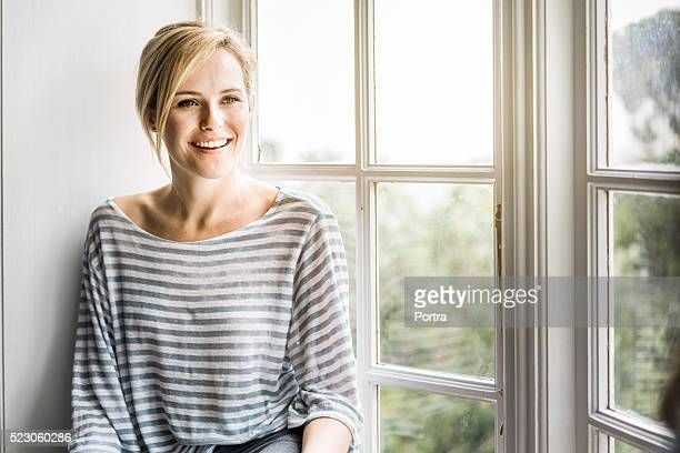 beautiful woman smiling by window at home - brightly lit stock photos and pictures