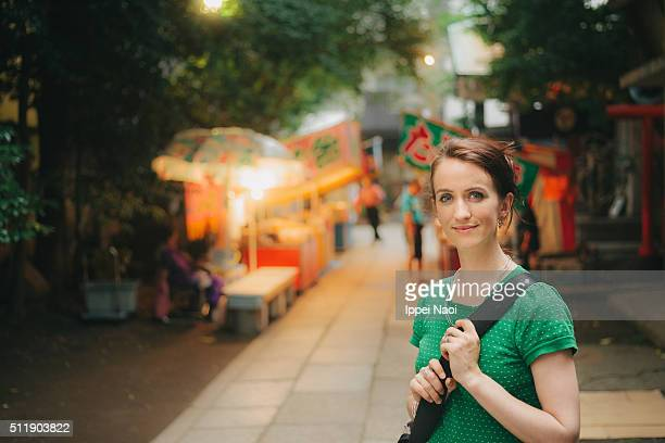 Beautiful woman smiling in an alley with festival food stands, Japan