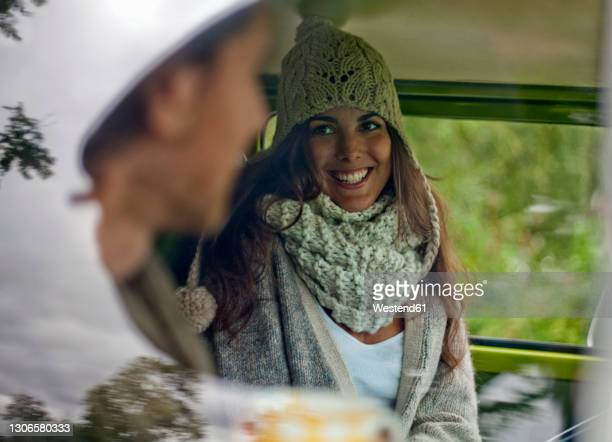 beautiful woman smiling while talking with boyfriend in campervan - women wearing see through clothing stock pictures, royalty-free photos & images