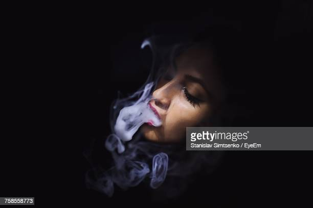 Beautiful Woman Smoking Cigarette Over Black Background