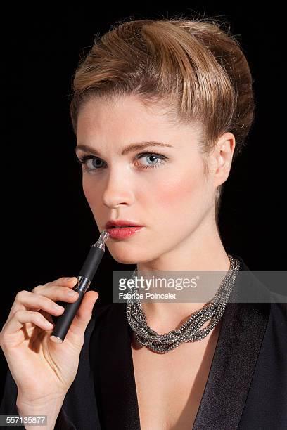 Beautiful woman smoking electronic cigarette