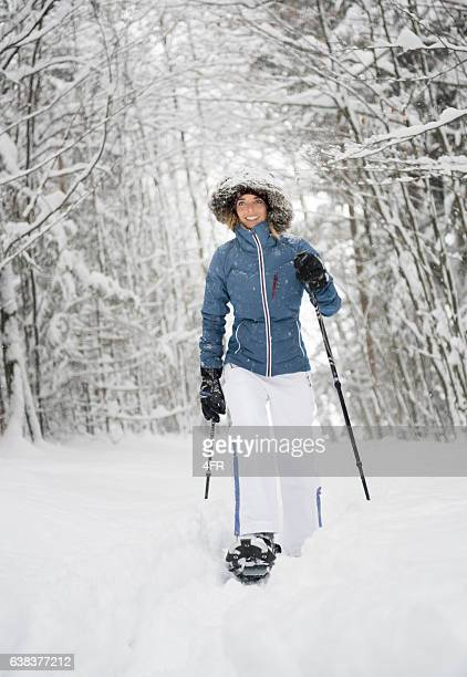 Beautiful Woman Snowshoeing through a Winter Forest
