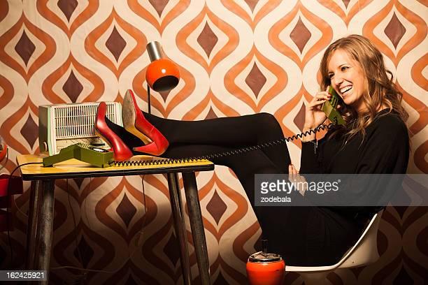 Hermosa mujer hablando por teléfono en la oficina Vintage