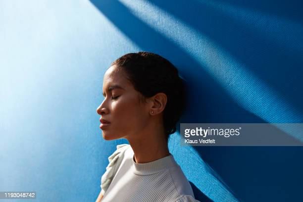beautiful woman standing against blue wall - wellbeing stock pictures, royalty-free photos & images