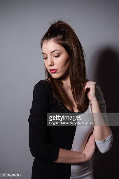 beautiful woman standing against gray background - bogdan negoita stock pictures, royalty-free photos & images