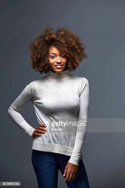 beautiful woman standing against gray background - long sleeved stock pictures, royalty-free photos & images
