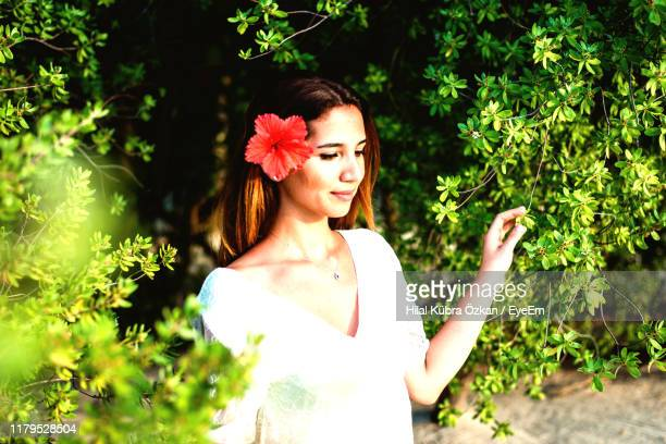 beautiful woman standing against plants in park - hilal stock photos and pictures