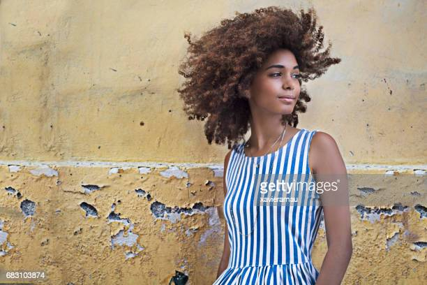 beautiful woman standing against wall looking away - striped dress stock photos and pictures