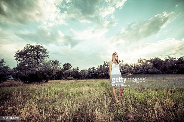 a beautiful woman standing in a field looking at the sky - robb reece fotografías e imágenes de stock