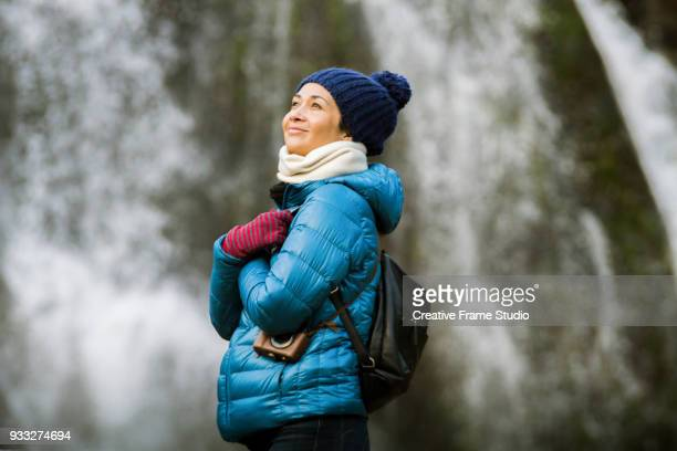 Beautiful woman standing in front of an spectacular waterfall in winter time