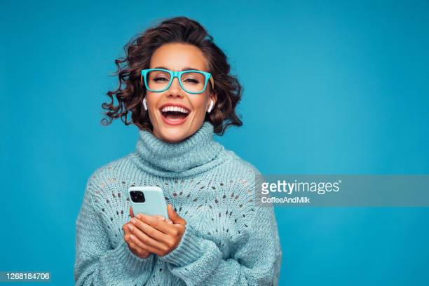 beautiful woman standing in front of blue background with smart phone - spectacles stock pictures, royalty-free photos & images
