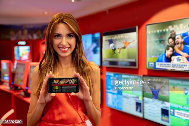 Beautiful woman standing next to live sports betting at the casino while holding a smartphone showing her bets