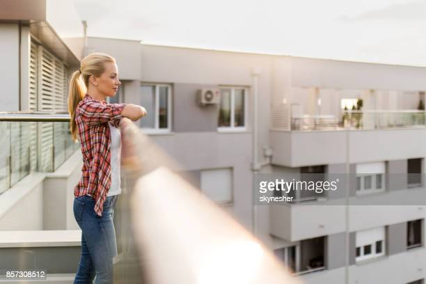beautiful woman standing on a penthouse terrace and enjoying the view. - women of penthouse stock photos and pictures