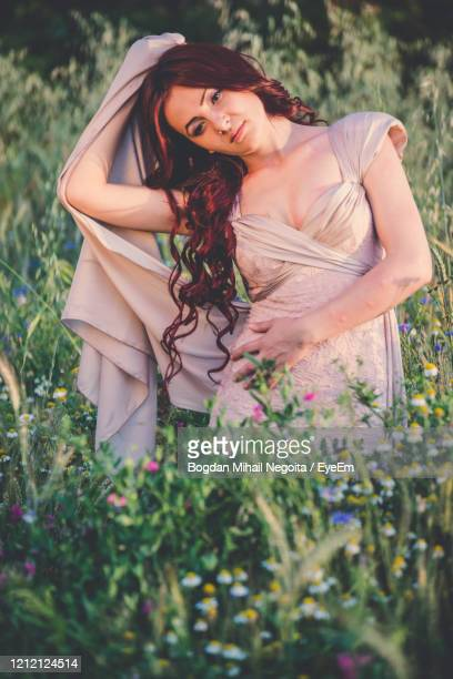 beautiful woman standing on field - bogdan negoita stock pictures, royalty-free photos & images