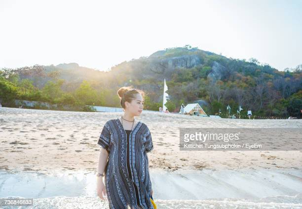 Beautiful Woman Standing On Shore At Beach Against Sky