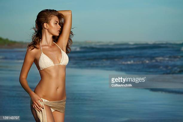 beautiful woman standing on the beach - erotiek stockfoto's en -beelden