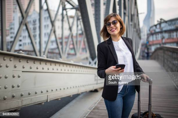 beautiful woman standing on the bridge with suitcase - business travel stock pictures, royalty-free photos & images
