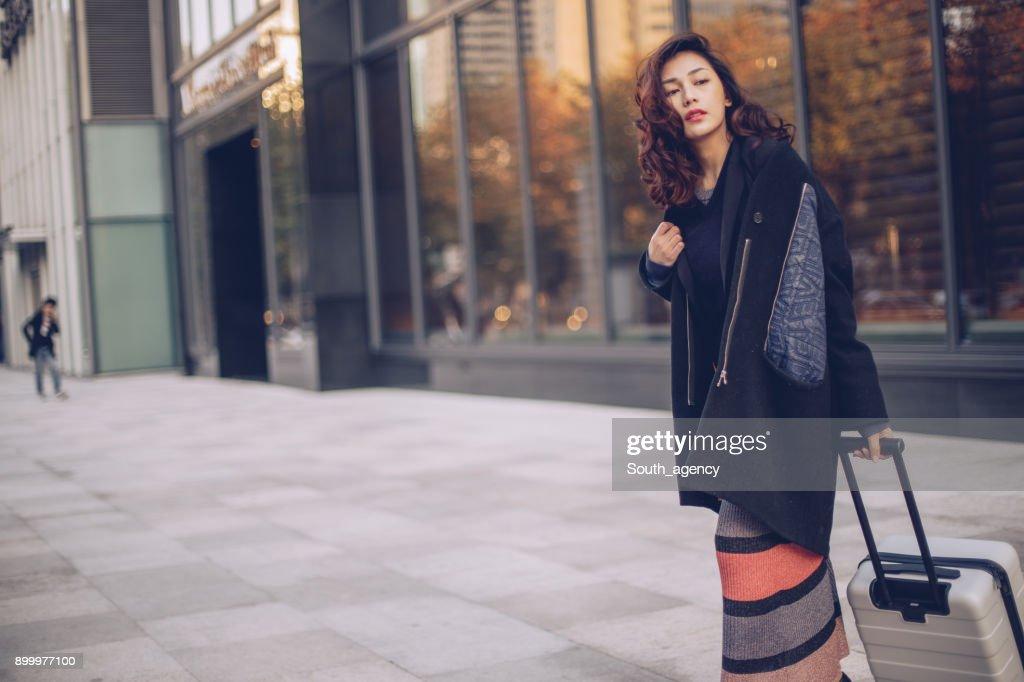 スーツケースを持って路上に立っている美しい女 : ストックフォト