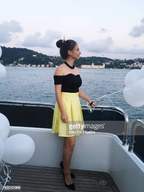 beautiful woman standing with balloons on yacht in sea against sky - off shoulder stock pictures, royalty-free photos & images