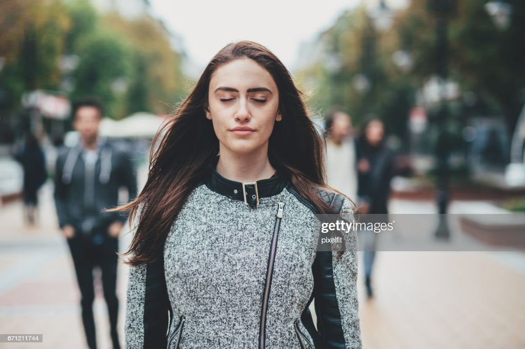 Beautiful woman standing with eyes closed on the street : Stock Photo