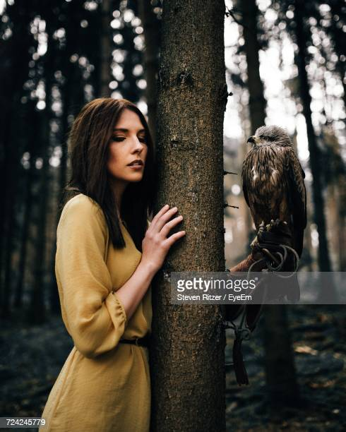 Beautiful Woman Standing With Hawk By Tree In Forest