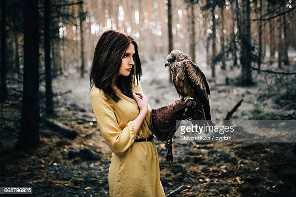 Beautiful Woman Standing With Hawk In Forest