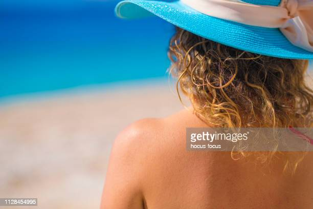 beautiful woman sunbathing at beach on summer - uv protection stock pictures, royalty-free photos & images