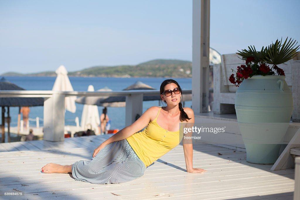 Beautiful woman sunbathing on a porch : Stock Photo