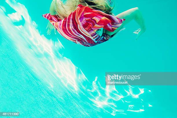 Beautiful woman swimming underwater playing peek-a-boo with a striped scarf.
