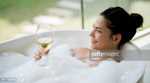 beautiful woman taking a bath and drinking a glass of wine - bubble bath stock pictures, royalty-free photos & images