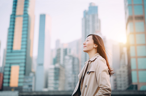 Beautiful woman taking a deep breath on city office roof terrace on a fresh morning - gettyimageskorea