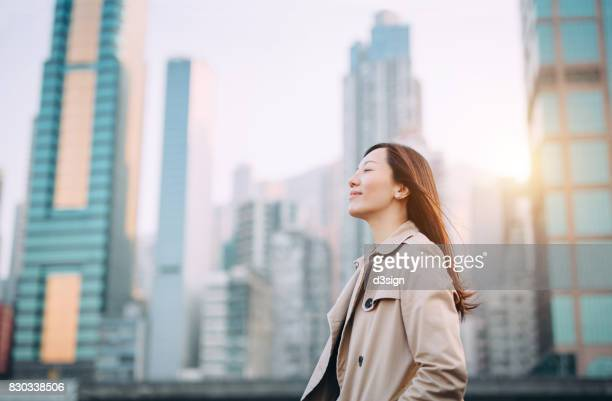 Beautiful woman taking a deep breath on city office roof terrace on a fresh morning