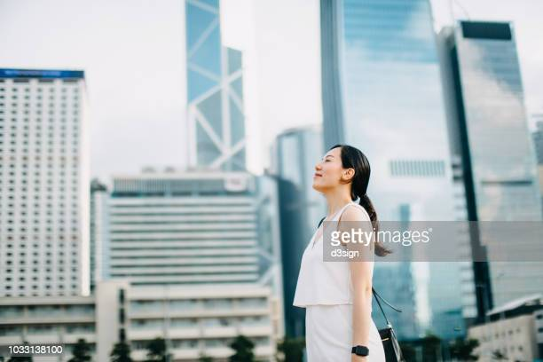 Beautiful woman taking a deep breath with eyes closed against urban cityscape in financial district