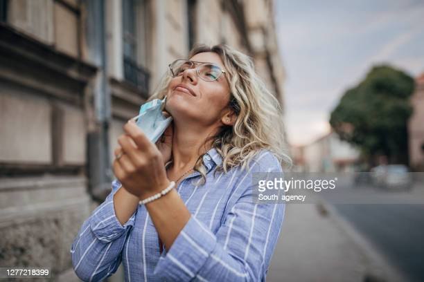 beautiful woman taking off protective mask on face on the street - removing stock pictures, royalty-free photos & images