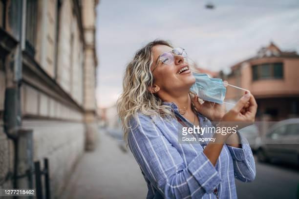 mulher bonita tirando máscara protetora no rosto na rua - strip - fotografias e filmes do acervo