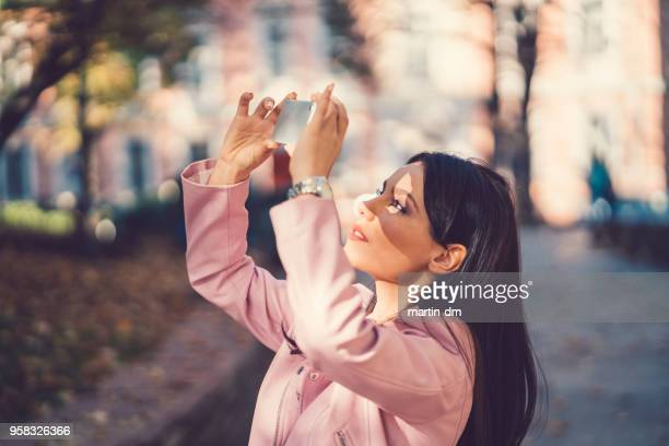 beautiful woman taking selfie in the park - martin dm stock pictures, royalty-free photos & images