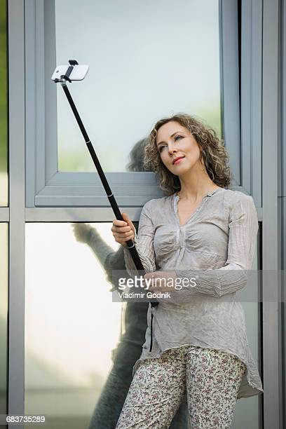 Beautiful woman taking selfie with monopod while leaning against glass windows