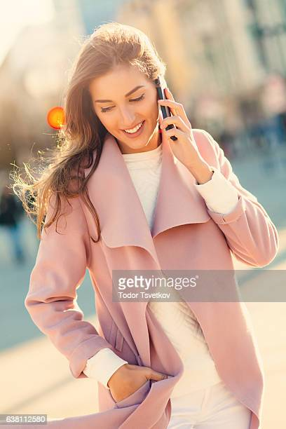 beautiful woman talking on the phone - hands in pockets stock pictures, royalty-free photos & images