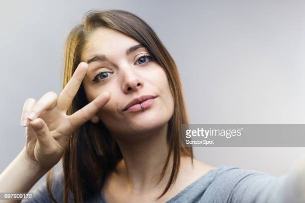 Beautiful woman talking selfie against gray background.