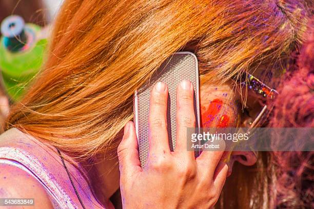 Beautiful woman talking with smartphone on ear covered with Gulal colorful powder in the Holi festival of Barcelona Catalonia Europe