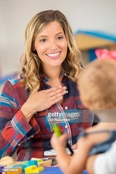 Beautiful woman teaching preschooler sign language