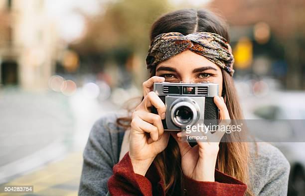 Hermosa mujer haciendo burla con cámara retro.