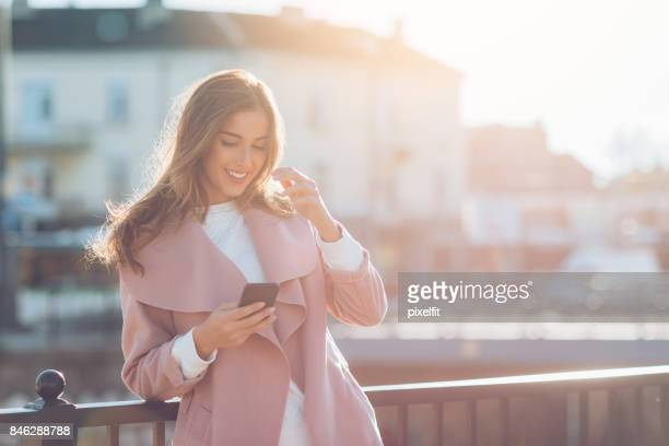 beautiful woman texting at sunlight - candid forum stock pictures, royalty-free photos & images